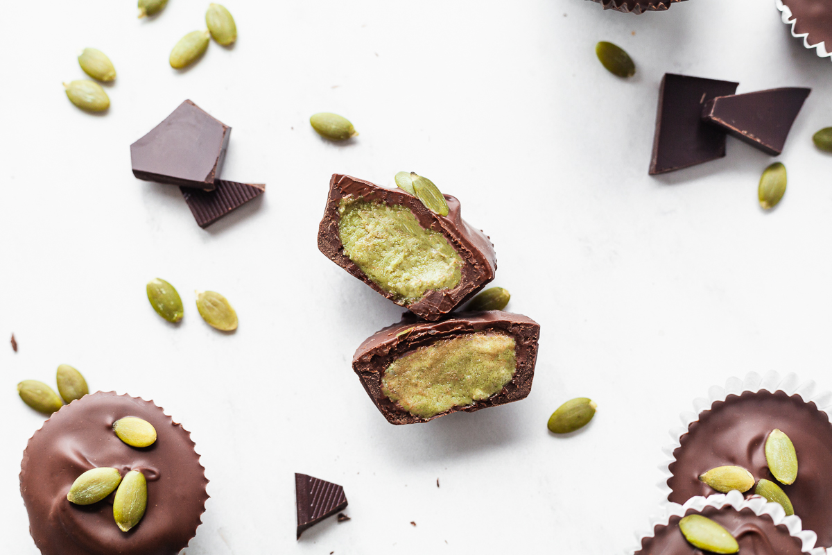 pumpkin seed butter cups surrounded by chocolate and pumpkin seeds