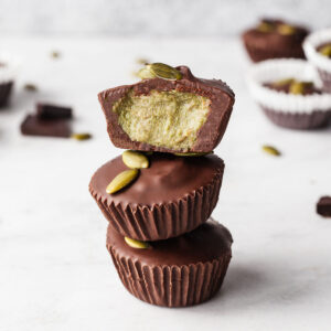 a stack of three pumpkin butter cups with the top one cut in half showing the green pumpkin butter inside
